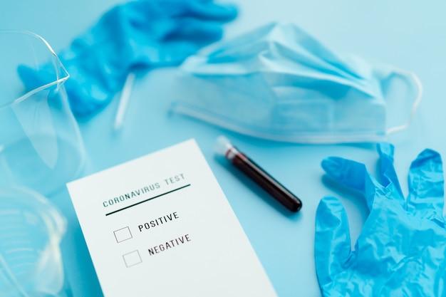 Dokument wyniku testu wirus korony na niebieskim tle z lekarz niebieskie rękawiczki i maskę