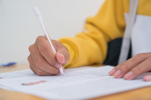 Dokument zgłoś biznes zajęty koncepcja: azjatycki starszy biznesmen lub student uniwersytetu czytający dokumenty zgłasza dokumenty przed podpisaniem stosów papieru w domowym biurze za pomocą pióra i papierkowej roboty