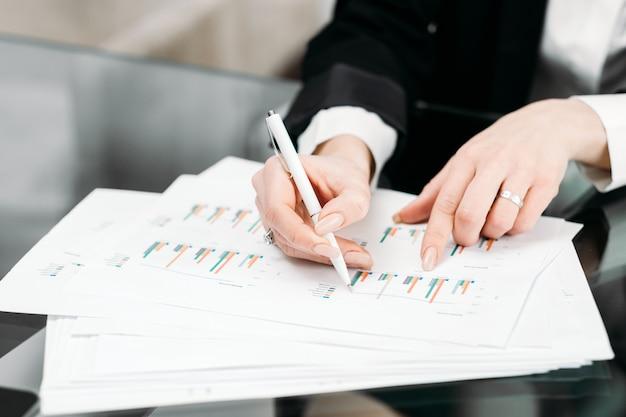 Dokumentacja biznesowa .. dokumenty studyjne pracownika biurowego z wykresami i wykresami, robienie notatek