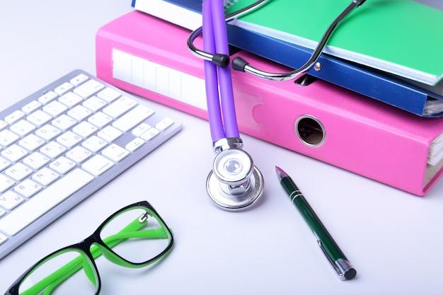 Dokumentacja medyczna z stetoskopem nad stosem folderów. klawiatura, okulary, długopis, recepta rx. selektywne ustawianie ostrości
