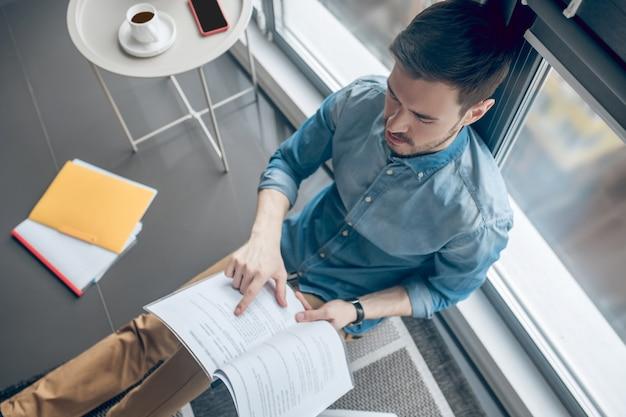 Dokumentacja projektu. młody biznesmen analizujący dokumentację projektu i wyglądający na zaangażowanego