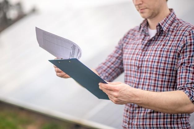 Dokumentacja, uwaga. ręce człowieka w koszuli w kratę, trzymając niebieski folder z dokumentami stojąc na świeżym powietrzu w pobliżu specjalnego obiektu.