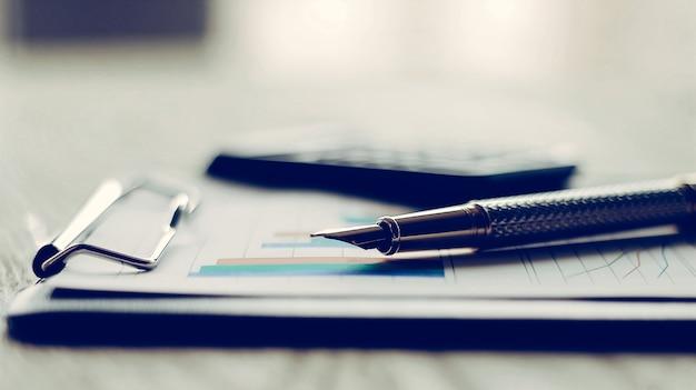 Dokumenty biznesowe z wykresem wzrostu, kalkulatorem i długopisem.