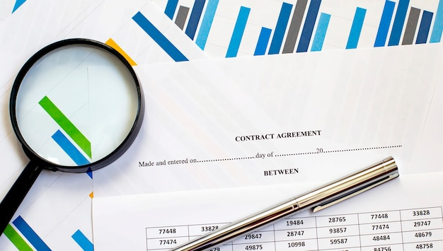 Dokumenty dotyczące wykresów biznesowych i analizy wykresów z panoramą i lupą umieszczoną na biurku