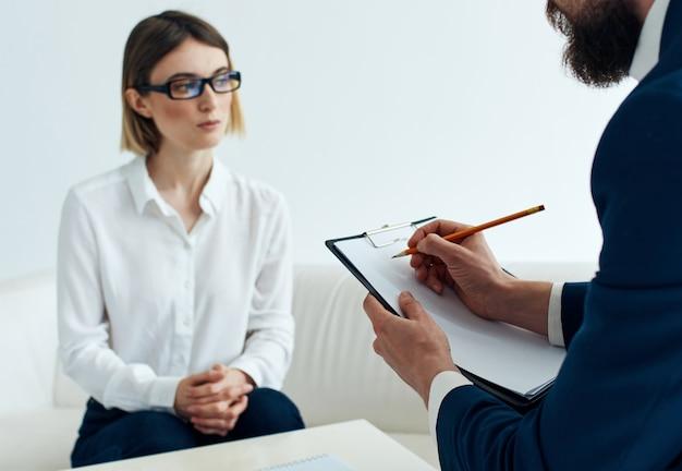 Dokumenty kobiety na kanapie i biznesmena w biurze