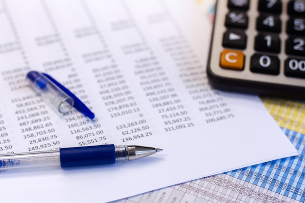 Dokumenty księgowości biznesowej z kalkulatorem i piórem.