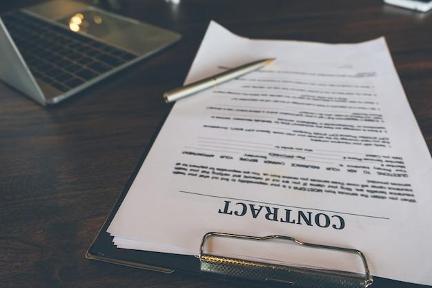 Dokumenty umowy i pióro z laptopem na drewniane biurko, umowa prawna