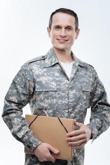 Dokumenty wojskowe. miły pozytywny żołnierz uśmiecha się i patrzy na ciebie, trzymając ważne dokumenty w swoim folderze