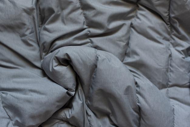 Dół kurtki tkaniny tło, szara kurtka puffer tekstura