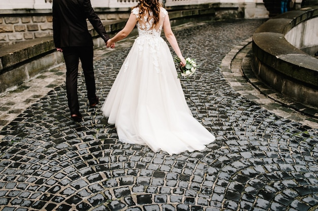 Dół sukni panny młodej i garnituru pana młodego na starym mieście. nowożeńcy z ślubnym bukietem kwiatów wracają do pałacu na starym kamiennym bruku.