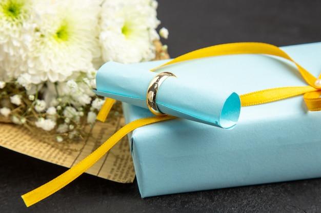 Dół zamknij widok pierścionek zaręczynowy zwój papier życzeń na prezent bukiet kwiatów na ciemnym tle