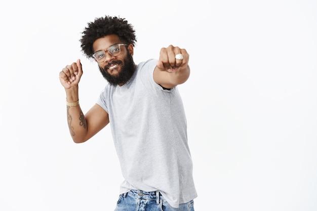 Dołącz do mnie w konkursie tanecznym. portret szczęśliwego enegized dobrze wyglądającego afroamerykańskiego faceta w okularach z pierścionkiem i przekłutym nosem uśmiechający się, ciągnąc pięść w kierunku kamery podczas tańca, ściskając ręce