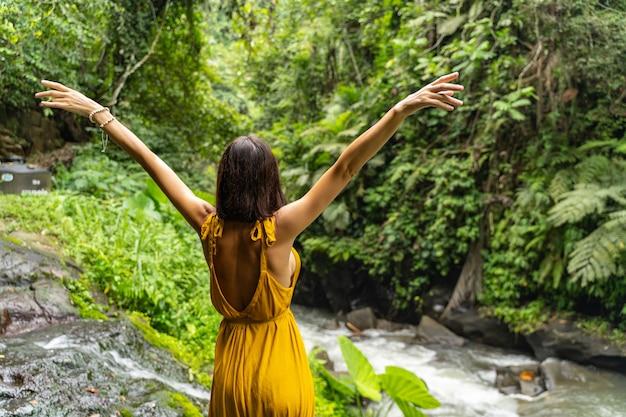 Dołącz do mnie. wesoła brunetka kobieta patrząca na zielone rośliny stojąc na dużym kamieniu
