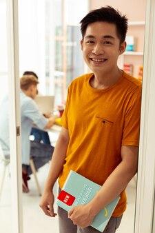 Dołącz do mnie. zachwycony azjatycki student oparty o drzwi podczas wizyty w szkole językowej