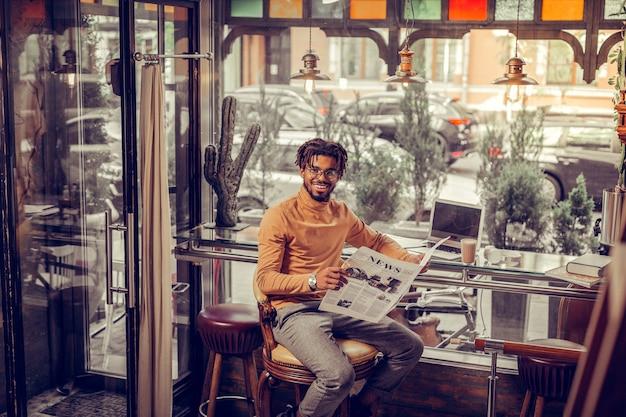 Dołącz do mnie. życzliwy freelancer z uśmiechem na twarzy podczas porannego przeglądu prasy