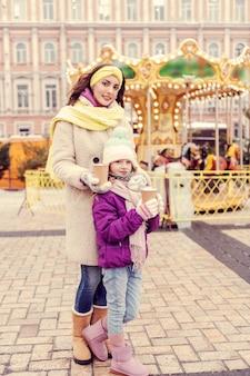 Dołącz Do Nas. Urocza Dziewczyna Trzyma Papierowy Kubek W Obu Dłoniach, Stojąc Blisko Swojej Mamy Premium Zdjęcia
