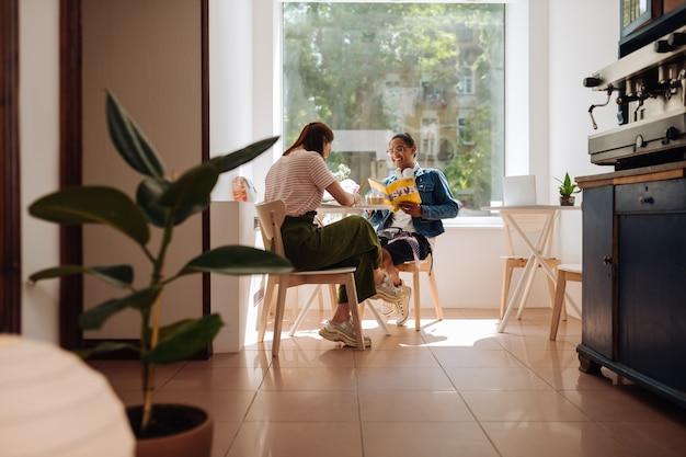 Dołącz do nas. zachwyceni koledzy z grupy siedzą w kawiarni przygotowując się do egzaminu