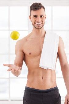 Dołącz do zdrowego stylu życia! przystojny młody muskularny mężczyzna z ręcznikiem na ramieniu, rzucający jabłko i uśmiechający się do kamery