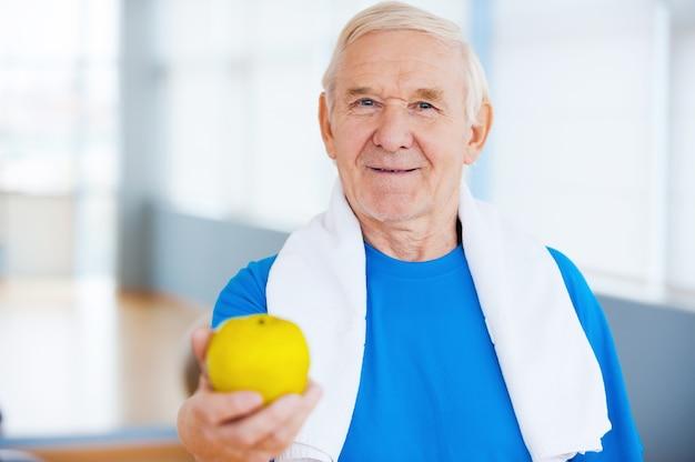 Dołącz do zdrowego stylu życia! szczęśliwy starszy mężczyzna z ręcznikiem na ramionach wyciągający zielone jabłko stojąc w klubie fitness