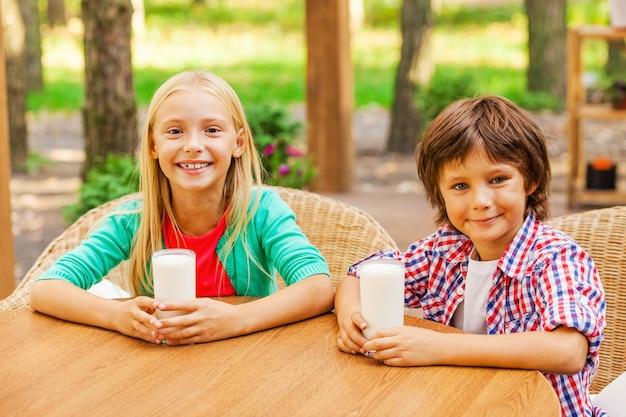 Doładowanie energii świeżym mlekiem. dwa słodkie małe dzieci pijące mleko i uśmiechające się, siedząc razem na świeżym powietrzu