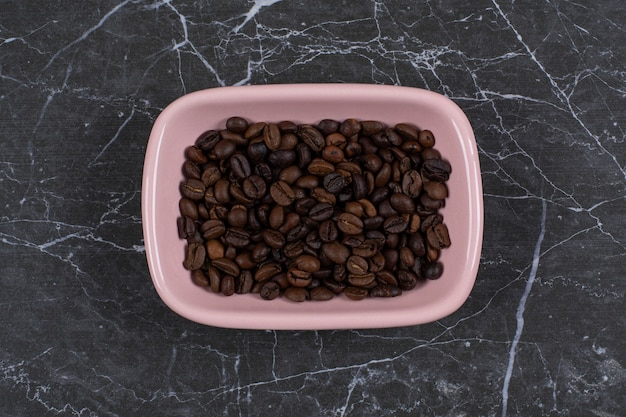 Doładuj zdjęcie brązowych nasion kawy w różowej misce.