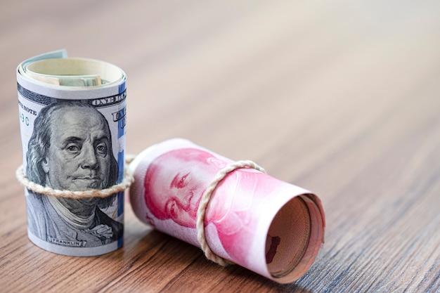 Dolar amerykański i juan banknot na drewnianym stole