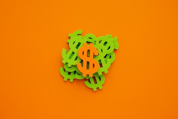 Dolar amerykański symbol na pomarańczowym tle. flatlay zielonych pieniędzy