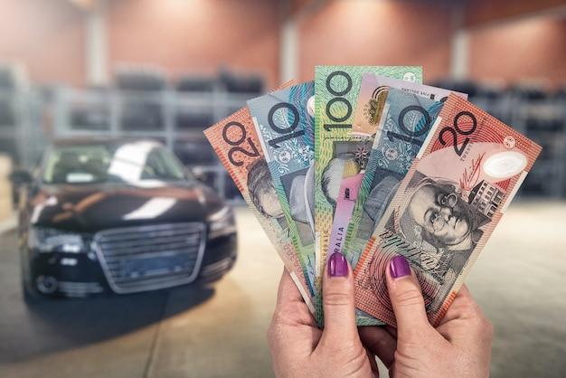 Dolar australijski w rękach na tle nowych samochodów