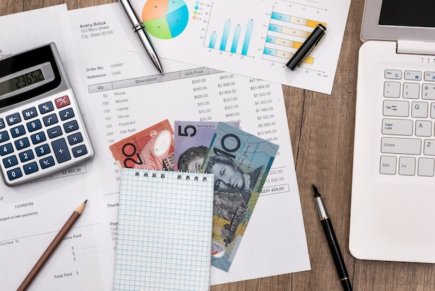 Dolar australijski z wykresem, laptopem z budżetem domowym i kalkulatorem