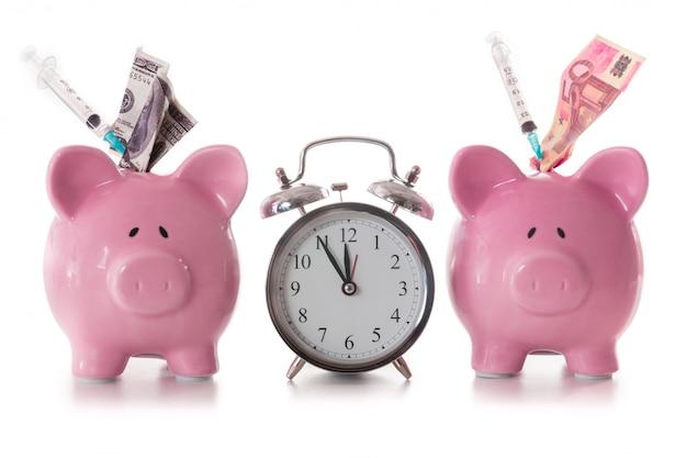 Dolar i euro notatki i strzykawki wtyka z prosiątko banków z budzikiem