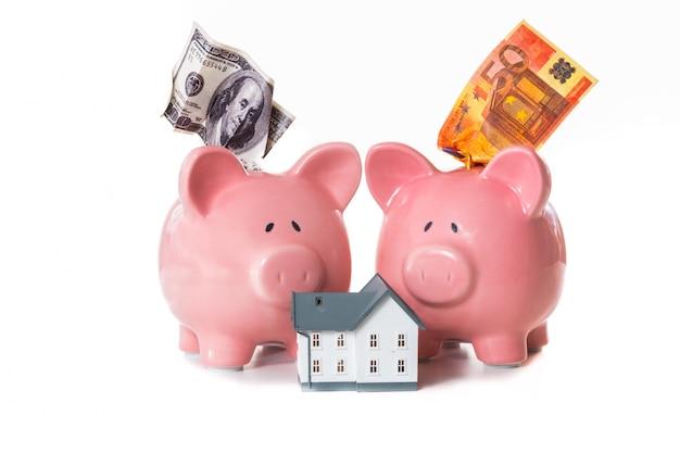 Dolar i euro notatki wystające ze skarbonki z modelu domu