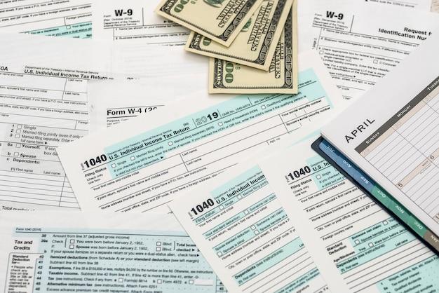 Dolar, kalkulator i długopis z formularzem podatkowym 1040