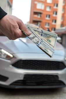 Dolar męskiej ręki wziąć pieniądze na tle samochodu koncepcja biznesowa