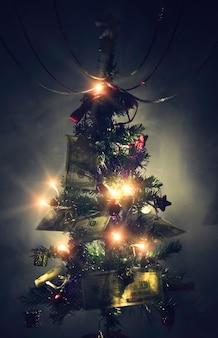 Dolar tło boże narodzenie, gałęzie sosny, noworoczna jodła ozdobiona jest 100 dolarami. studolarowe banknoty ułożone na gałęziach choinki jako prezent od świętego mikołaja.