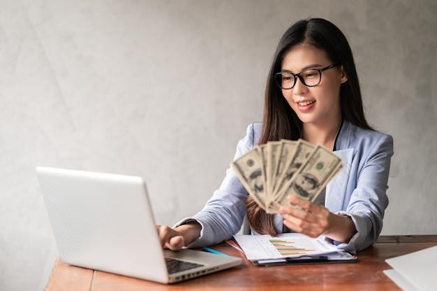 Dolar w dłoni bizneswoman. kobieta z azji pracuje w domu lub w biurze i jest zadowolona z tego, że otrzymuje dolarowe pieniądze z pracy i dodatkowej kariery lub samozatrudnienia w niepełnym wymiarze godzin.