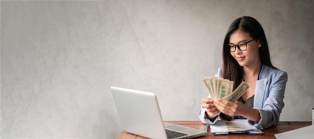 Dolar w ręce bizneswoman. kobieta z azji pracuje w domu lub w biurze i cieszy się, że może zarobić w dolarach z pracy i dodatkowej kariery