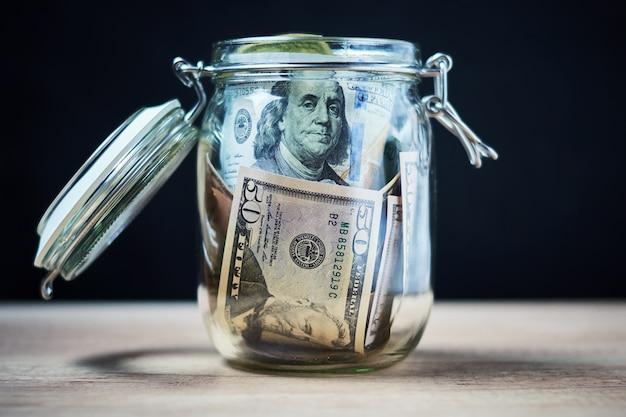Dolarów amerykańskich rachunki w szklanym słoju. oszczędzanie pieniędzy i koncepcja inwestycji