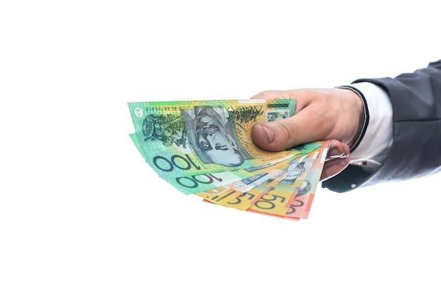Dolarów australijskich w męskiej dłoni na białym tle