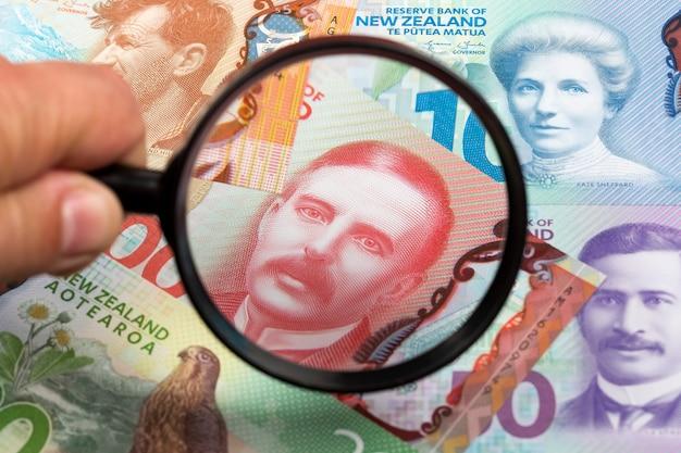 Dolarów nowozelandzkich na tle szkła powiększającego