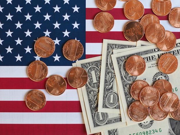 Dolarowe banknoty i monety oraz flaga stanów zjednoczonych