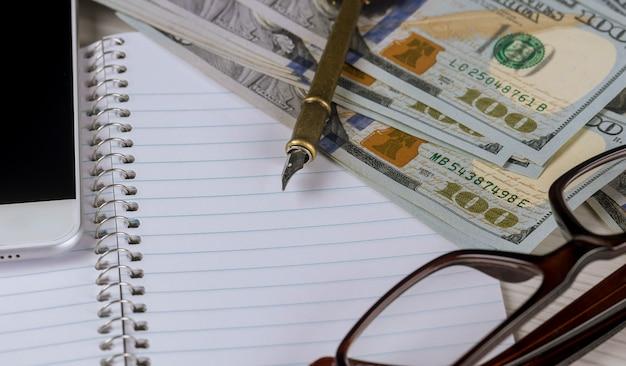 Dolarowe banknoty, zbliżenie leżą na białej kartce papieru obok pióra i okularów w plastikowej ramie