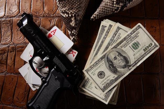 Dolarowe notatki i pistolet, czarny pistolet