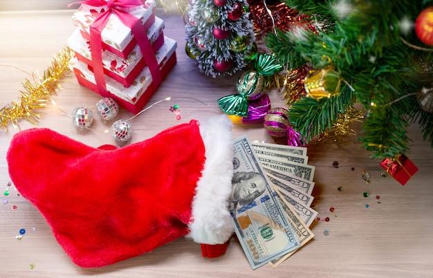 Dolarowi banknoty w santa skarpecie i bożenarodzeniowym dekoraci tle