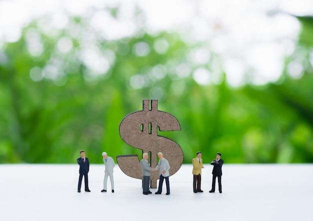 Dolarowy znak za miniaturowym biznesmena handshaking, dyskutujący, negocjujący.