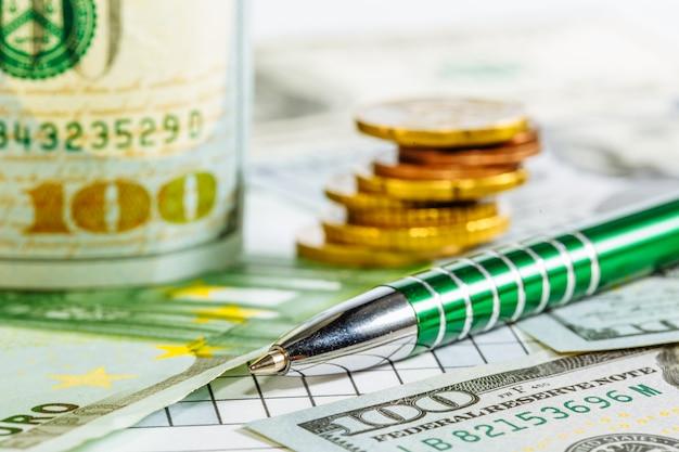 Dolary amerykańskie. banknoty euro. monety długopis obok rachunków. pieniądze. waluta. tło z pieniędzmi. dolar.