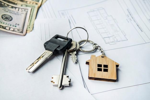 Dolary amerykańskie i klucz do domu na planie architektonicznym mieszkania. sprzedaż i zakup nieruchomości, zakup koncepcji domu. koncepcja kupna sprzedaży lub wynajmu domu.