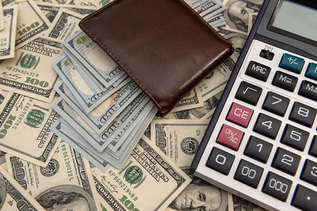 Dolary amerykańskie w portfelu z kalkulatorem. koncepcja biznesowa finansowe.