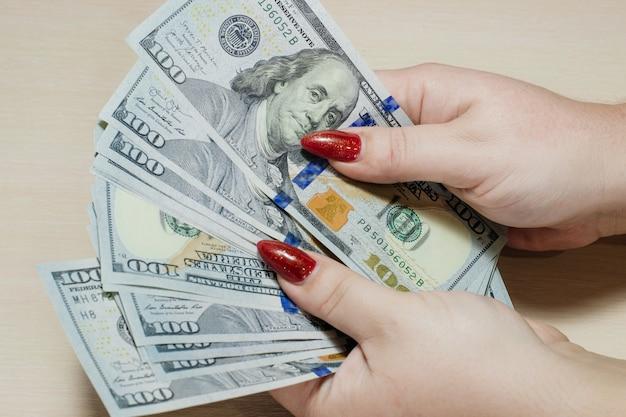Dolary amerykańskie w rękach kobiet. człowiek liczący pieniądze, pojęcie gospodarki światowej.