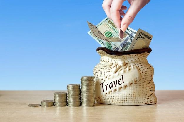 Dolary amerykańskie w torbie z monetami stos na stole, rozmycie tła. koncepcja oszczędzania pieniędzy na podróże.