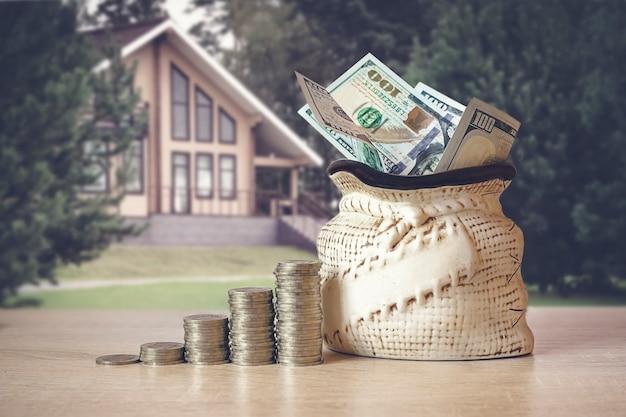 Dolary amerykańskie w torbie z monetami stos na stole, rozmycie tła z prywatnego domu. koncepcja oszczędzania pieniędzy, finansowych. pomysły inwestycyjne, zarządzanie finansami na przyszłość. koncepcja rozwoju biznesu.